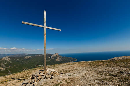 Christian wooden cross on mountain top, rocky summit, beautiful inspirational landscape with ocean, clouds and blue sky, looking at scenic blue sea and white clouds