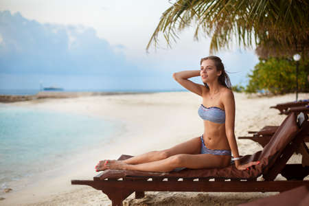 Young woman relaxing in a deck chair on a tropical beach at sunrise or sunset with stylish straw hat on, girl on a beach sun bed chilling near ocean and palms on Maldives