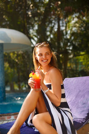 Portrait of young woman with cocktail glass near swimming pool on a deck chair with palm trees behind. Vacation concept