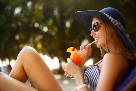 Portrait of young woman with cocktail glass chilling in the tropical sun near swimming pool on a deck chair with palm trees behind. Vacation concept Stock Photo