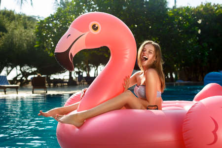 Young and sexy girl having fun and laughing on an inflatable giant pink flamingo pool float mattress in a bikini. Attractive tanned woman lies in the sun on vacation