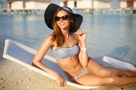 sunhat: Young woman relaxing in a modern deck chair on a tropical beach with stylish straw hat and sunglasses on. Girl is sitting on a beach sun bed chilling near ocean, palms and bungalows Stock Photo