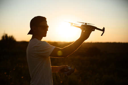 Silhouette of a man holding small compact drone and remote controller in his hands. Pilot launches quadcopter from his palm on sunset. Drone ready to take off.