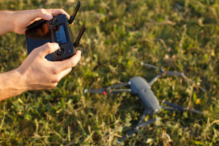 Man holds a drone remote controller in his hands. Quadcopter is on the ground ready to go and fly blurred on the background. Pilot is going to start motors and take off.