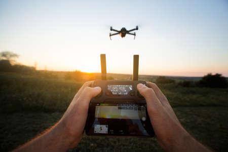 彼の手でリモコンを押しながら空中写真ビデオを撮る男の視点ショット。Quadcopter が背景に飛んでいます。ハメ撮り - サンセットのパイロットの前に
