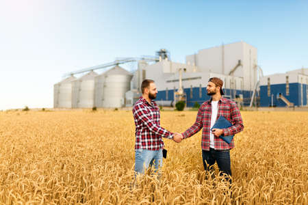People shaking hands in a wheat field, farmers agreement. Grain elevator terminal on background. Agriculture agronomist business contract concept