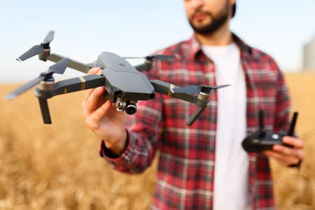Bearded hipster man shows small compact drone and holds remote controller in his hand. Farmer agronomist looks at quadcopter before the launch in a wheat field