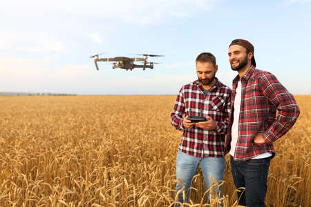 Compact drone hovers in front of two hipster men. Quadcopter flies near farmer and agronomist exploring harvest with innovative technology taking aerial photos and videos from above it wheat field