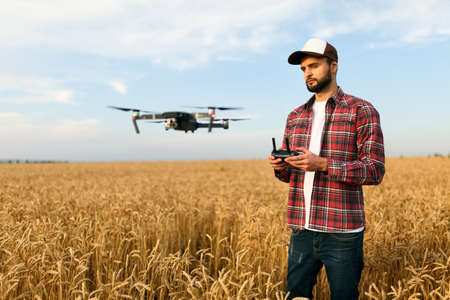 Compact drone hovers in front of farmer with remote controller in his hands. Quadcopter flies near pilot. Agronomist taking aerial photos and videos in a wheat field Stock Photo