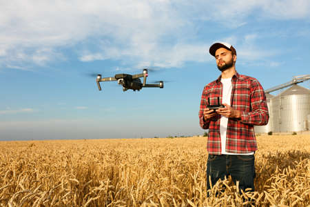 agronomist: Drone hovers in front of farmer with remote controller in hands near grain elevator. Quadcopter flies near pilot. Agronomist taking aerial photos and videos in a wheat field. Stock Photo