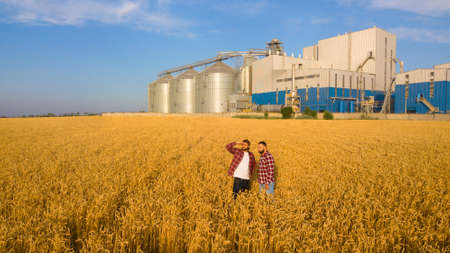 Aerial photo of two farmers standing in a wheat field and looking far discussing harvest and businness. Two men agronomists with grain elevator terminal on background. Agriculture theme Stock Photo