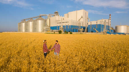People shaking hands in a wheat field, farmers agreement. Grain elevator terminal on background. Agriculture agronomist business contract concept. Aerial photo. Agriculture theme Stock Photo