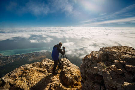 삼각대와 카메라 구름, 도시와 바다 위에 높은 산 피크에 서있는 사람. 록 키 정상 회의에서 dslr 설정을 조정하는 전문 사진 작가.