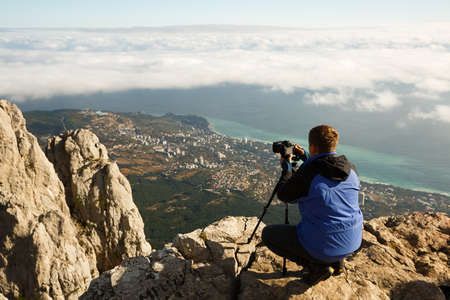 Man sitting with a tripod and photo camera on a high mountain peak above clouds, city and sea. Pro photographer adjusting dslr settings on rocky summit. Ai Petri, Yalta, Crimea.