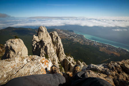 Traveler sitting on a cliff of rocky mountain summit above clouds. Point of view photo of legs in hiking boots with sea, city and mountain landscape. Ai Petri, Yalta, Crimea.