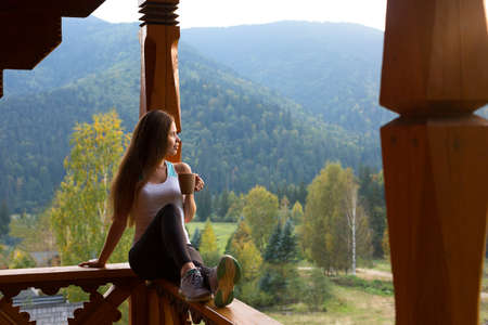 Woman leaning on wooden handrail and enjoys and relaxes beautiful mountain scenic. Young female on terrace sitting on handrail with a cup of tea or coffee