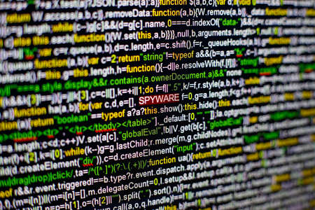 Macro photo of computer screen with program source code and highlighted SPYWARE inscription in the middle. Computer script on the screen with virus in it. Cyber security concept. Stock Photo