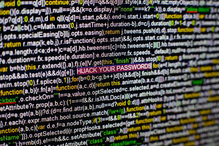 Macro photo of computer screen with program source code and highlighted HIJACK YOUR PASSWORDS inscription in the middle. Computer script on the screen with virus in it. Cyber security concept.