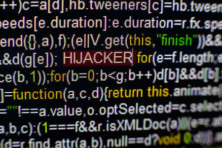 Macro photo of computer screen with program source code and highlighted HIJACKER inscription in the middle. Computer script on the screen with virus in it. Cyber security concept. Stock Photo