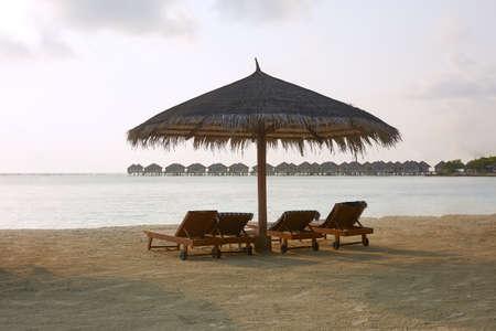 Beach deck chairs under straw umbrellas. Indian ocean coastline on Maldives island. White sandy beach and calm sea. Travel and vacation concept.