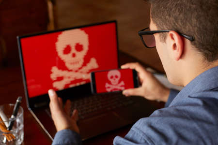 Man sits near laptop with phone blocked and encrypted by ransomware spyware asking for money. Laptop and smartphone infected by virus. Scary red skull crossbones on screen. Cyber security concept.