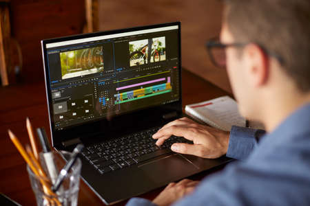Freelancer video editor works at the laptop computer with movie editing sofware. Videographer vlogger or blogger camera man at work editing vlog. Tracking and revealing shot Foto de archivo