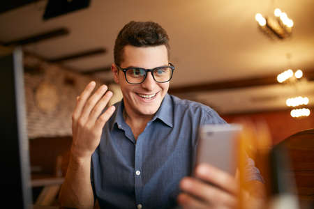 Surprised freelancer hipster man looks to smartphone and can not believe he won lottery prize or money in trading cryptocurrency. Pop-eyed successfull amazed businessman trader. Video call conference Archivio Fotografico
