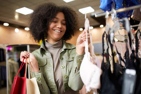Young smiling attractive african american woman choosing right bra size in lingerie store. Black mixed race pretty girl considers underwear in shop and holding paper shopping bags.