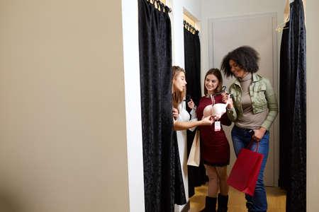 Schöne junge Frau, die um Freundmeinung in der Umkleidekabine bittet