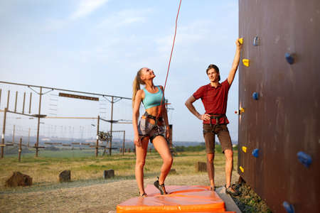 Instructor man guiding pretty slim caucasian woman on rock climbing training wall outdoors. Healthy lifestyle and leisure concept.