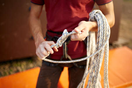 A rock climber tie a knot on a rope. A person is preparing for the ascent. Man learns to tie a knot near climbing wall. Checking the insurance for climbing. Stock Photo