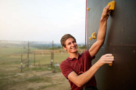Sporty man practicing rock climbing in gym on artificial rock training wall outdoors. Young talanted smiling climber guy on workout looks to camera