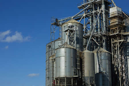 Modern grain terminal. Metal tanks of elevator. Grain-drying complex construction. Commercial grain or seed silos at seaport. Steel storage for agricultural harvest.