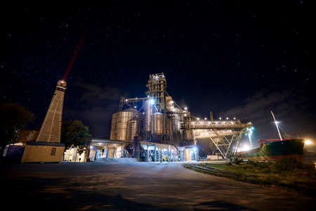 Grain terminal at seaport with starry sky on background. Cereals bulk transshipment from road transport to vessel at night. Loading grain crops on ship from elevators at the berth. Long exposure.