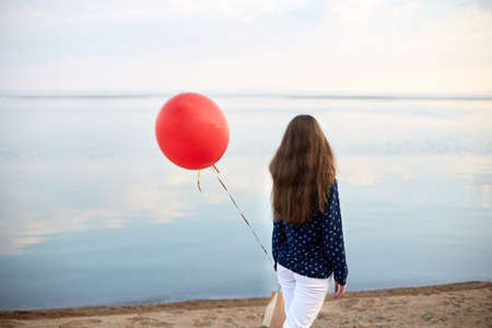 Portrait of young woman with red air balloon and present bag near the calm sea or lake shore. Clouds are reflected on the smooth water surface. Girl on her birthday. Copyspace. Holiday concept. Stock Photo