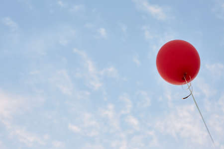 Red helium air balloon with calm blue cloudy sky on background. Peace and holiday concept. Bottom view. Copyspace for minimalistic design. Stock Photo