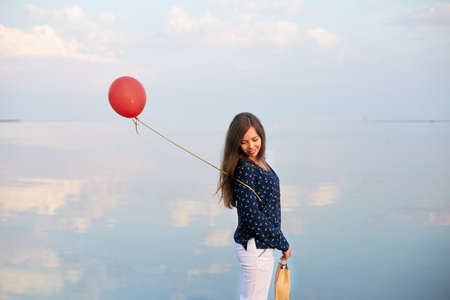 Minimalistic portrait of young woman with red air balloon and present bag near the calm sea or lake shore. Clouds reflected on smooth water surface. Girl on her birthday. Copyspace. Holiday concept. Stock Photo