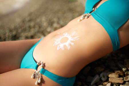 Sunscreen lotion drawn on tanned woman belly skin as sun shape. Suntan cream applied on body. Suncream on stomach. Woman wearing bikini swimsuit sunbathing on the beach. Skin care health concept.