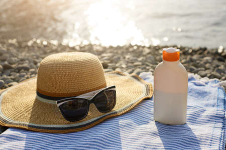 Suntan cream bottle and sunglasses on beach towel with sea shore on background. Sunscreen on deck chair outdoors on sunrise or sunset. Skin care and protection concept. Golden tan. Stock Photo