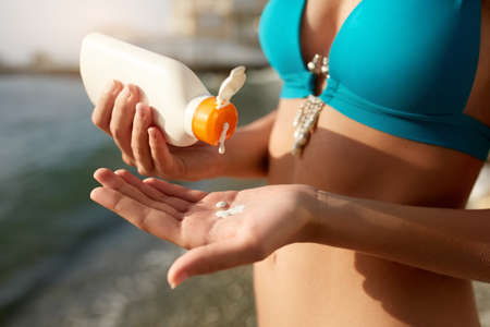 Woman hands putting sunscreen from a suntan cream bottle. Caucasian female squeeze suncream on her hand. Tanned girl wearing blue bikini swimsuit on the beach. Skin care and protection concept.
