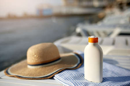 Suntan cream bottle on beach towel with sea shore on background. Sunscreen on deck chair outdoors on sunrise or sunset at luxury spa resort. Skin care and protection concept and travel. Golden tan.