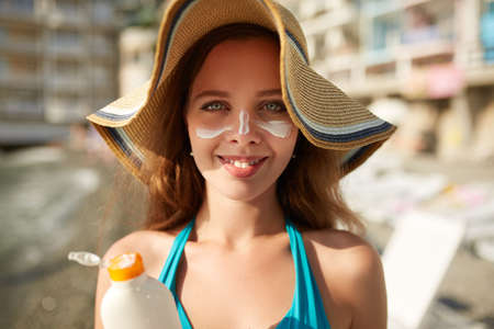 Suntan lotion. Woman applying sunscreen solar cream on face. Beautiful happy cute girl puts suntan cream from plastic container bottle on her nose and cheecks. Female in straw hat and bikini on beach. Stock Photo