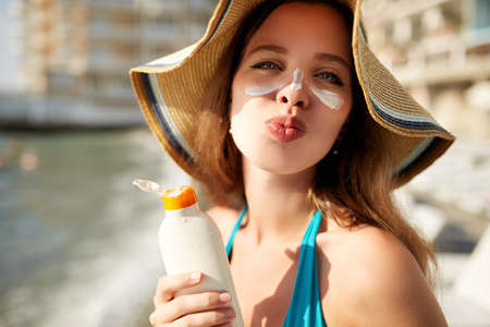 Suntan lotion. Cute woman applying suntan cream sunscreen solar from plastic container bottle on her nose and cheecks. Female in straw hat and bikini with big lips sends kiss to camera on beach.