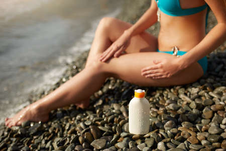 Slim woman tanned lower body in shape lying on pebble beach near sea waves and surf with sunblock cream bottle. Girl applies water resistant sunscreen lotion on legs relaxing in sun holiday.