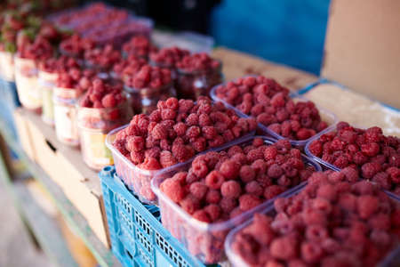 Raspberries on a farm market in the city. Fruits and vegetables at a farmers summer market.