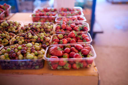 Gooseberry and strawberry on a farm market in the city. Fruits and vegetables at a farmers summer market. Stock Photo