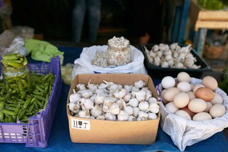 Display of fresh green and white onions, garlic, eggs, peas and pumpkin seeds. Fruits and vegetables at a farmers summer market. Stock Photo