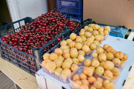 Sweet cherry and apricot on a farm market in the city. Fruits and vegetables at a farmers market. Cherries in boxes and trays