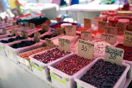 Different kinds of beans and dried fruits on sale at the local farmers summer market outdoors. Natural organic food on market place.