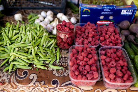 Raspberries, garlic and peas on a farm market in the city. Fruits and vegetables at a farmers summer market.